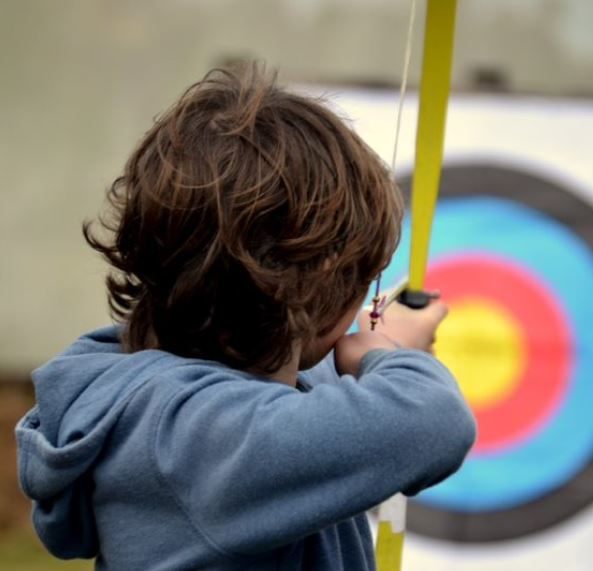 Boy learning archery at School Holiday Club at Via Ferrata Cornwall