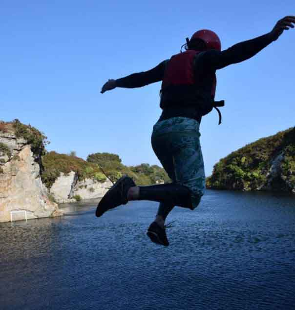 Man leaping into the quarry water during a coasteering session at Via Ferrata Cornwall