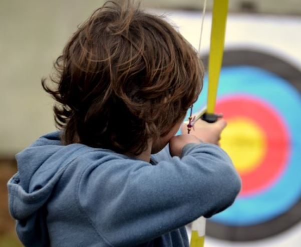 Boy taking aim in an archery session