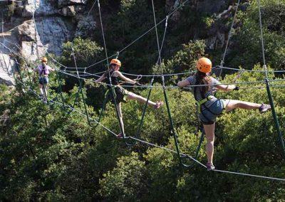 Girls balance on the High Wire Bridge at Via Ferrata Cornwall