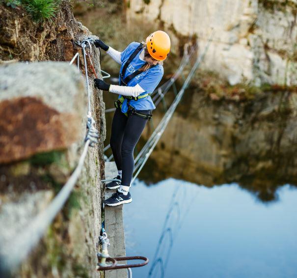 Teen girl traversing the cliff face at Via Ferrata Cornwall