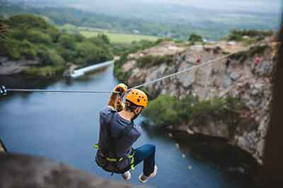 Man on the zip wire flying over the water at Via Ferrata Cornwall