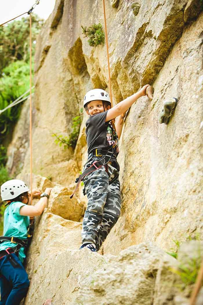 Boys climbing up rockface smiling